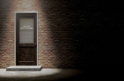 Private Eye Door Outside. A 3D render of a wooden door on a face brick building with a closed shutter, a private investigator written on it highlighted by an Royalty Free Stock Photography