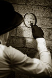 Private Eye Searching For Clues. Retro Private Eye Detective Searching For Clues By Investigating A Suspected Crime Scene Wall With A Magnifying - Looking Glass Royalty Free Stock Photos
