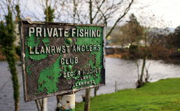 Private Fishing sign, Wales. An old, iron, private fishing sign, set against trees and the river and riverbank royalty free stock photo