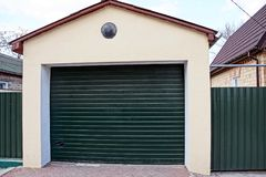 Garage with closed green gates and part of the fence in the street near the road. Private garage with closed green gates and part of the fence in the street at royalty free stock images