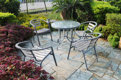 The  private garden. The glass tables and chairs in a private garden by the road Stock Photos