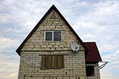 Gray brick house with window and satellite dish on the sky background Stock Photo