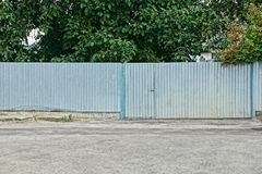 Gray long metal fence and closed door in the street near the asphalt road. A private gray long metal fence and a closed door in the street near the asphalt road stock photos