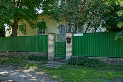 A green metal fence and a closed door on the street near the road. A private green metal fence and a closed door on the street near the road stock images