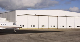Private hanger. Modern luxury private jet welcoming passengers at private hanger Stock Images