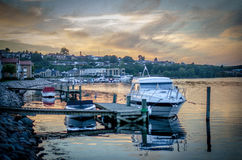 Private harbour area on a river front during sunset next to a small village Stock Photo