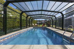 Private Heated Swimming Pool & Enclosure. A large private heated swimming pool in the garden of a large country property in a village in Yorkshire in northeast Royalty Free Stock Photos
