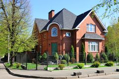 Private house. Two story red brick private house with lawn and trees royalty free stock photo