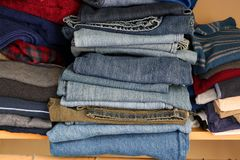 Private house closet with well organized casual man clothes. Shelf with pail of jeans and jumpers in the closet. Blue denim background. Casual lifestyle concept stock image