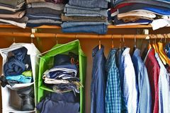 Private house closet with well organized casual man clothes. Man wardrobe with variety of shirts hung on hangers and pile of jumper, jeans and pants lain on a royalty free stock photo