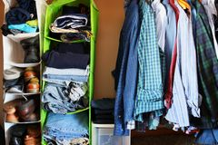 Private house closet with well organized casual man clothes. Man wardrobe with variety of shirts hung on hangers, shoes and pile of jumper, jeans and pants lain royalty free stock photography