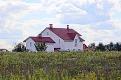 Private house among a green field against a blue sky Royalty Free Stock Photography