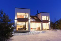 Private house with panoramic windows in a modern style on a back. Ground of the night sky Stock Photos