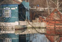 Private houses barn shed sunken underwater flooded during the spring flood flow stream river the boat at the fence property Stock Photography