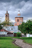 Private Houses and Church of Boris and Gleb before Storm Suzdal. SUZDAL, RUSSIA - View from paved stone walkway on the grounds of museum of Wooden Architecture royalty free stock image