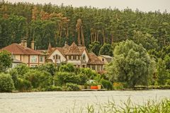 Private houses on the shore of a reservoir in green vegetation. Private houses on the lake in green vegetation and trees stock image