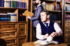 Private investigator and detective concept. Man with strict face. At tea party. Retro detective drinks tea in antique room, defocused. Men in suit, detectives stock photography