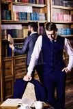 Private investigator and detective concept. Retro detectives work. On investigation in antique room or library with old bookshelves on background. Men in suit royalty free stock image