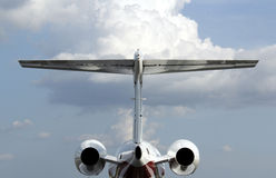 Private jet engine. A rear view of a private jet , engines and tail with a cloudy sky in background stock photography