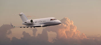 Private jet in the air. With clouds in the background Royalty Free Stock Images