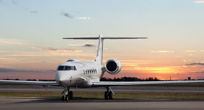 Private jet at the airport. At sunset or sunrise Stock Photo