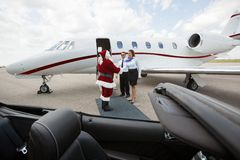 Private Jet Crew Greet Santa. Santa travelling on a private jet meeting cabin crew Royalty Free Stock Photo