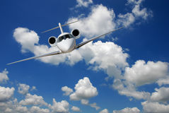 Private jet flying. Private jet against blue sky and clouds Stock Images