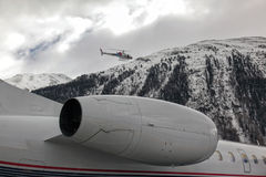 A private jet and a flying helicopter at the airport of St Moritz. A private jet and a flying helicopter in St Moritz Stock Photo