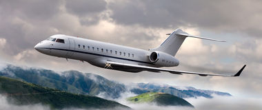 Private jet flying over mountains. With clouds around Stock Images