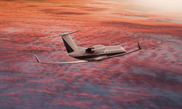 Private jet flying over a sunset sky. And turning Royalty Free Stock Photo