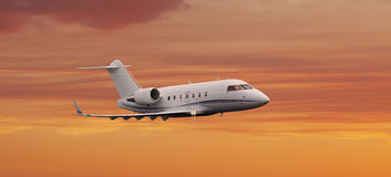 Private jet flying over a sunset sky. Up close Stock Photo