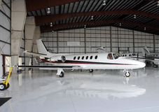 Private jet in hangar. Luxury private jet in hangar between flights stock images