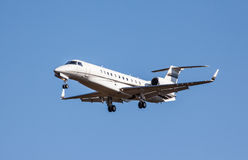 Private jet landing. Small private jet approaching KEF airport with landing gears down Stock Photos