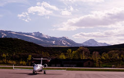 Private Jet and Mountains. Twin engine private jet aircraft on tarmac with snow covered mountains in distance Royalty Free Stock Photography