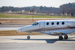 Private Jet Moving onto Runway by Wind Sock Royalty Free Stock Photo