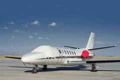 Private jet parked at airport. With blue sky Stock Photography
