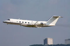 Private Jet plane. Low fly near the city stock photo