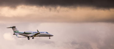 Private Jet Plane. Geneva, Switzerland. A private jet plane descending at Geneva International Airport in a cloudy weather. Picture can be used for articles in stock image