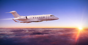 Private jet plane flying above clouds in sunset Royalty Free Stock Images