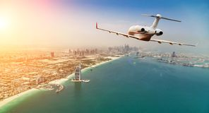 Private jet plane flying above Dubai city in beautiful sunset li. Ght. Modern and fastest mode of transportation, business life royalty free stock photography