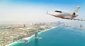 Private jet plane flying above Dubai city stock photo