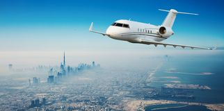 Private jet plane flying above Dubai city royalty free stock photography
