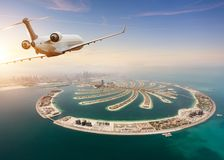 Private jet plane flying above Dubai city stock photos