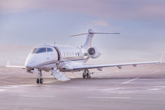Private jet plane parking at the airport. Private airplane at sunset, Royalty Free Stock Images