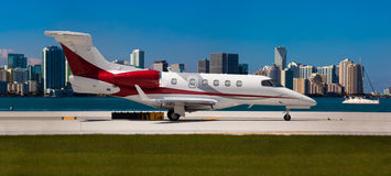 Private jet on the runway. With city in the background Royalty Free Stock Photos