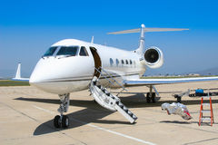 A private jet sits ready at the airfield. A private jet sits with door open ready to take on passengers royalty free stock photography