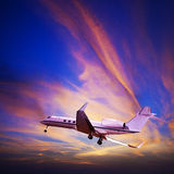 Private jet in a spectacular sunset sky. Private jet maneuvering in a spectacular sunset sky. Square composition Royalty Free Stock Images
