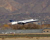 Private jet takeoff. Learjet taking off from small runway gear down Stock Images