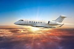 Private jetplane flying above clouds in sunset Royalty Free Stock Photography