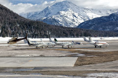 Private jets and a helicopter at the airport of St Moritz. Private jets and a helicopter in St Moritz stock photography